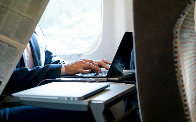 新幹線内でインターネットをする男性のイメージ