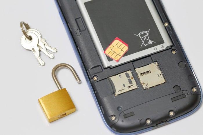 スマホとSIMと鍵と南京錠が置いてあるイメージ