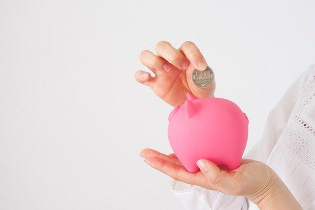 貯金箱と女性の手