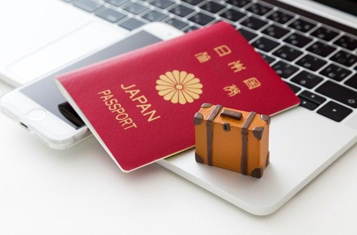 ノートパソコンの上にあるスマホとパスポート