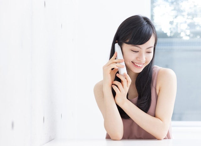 固定電話で電話する女性