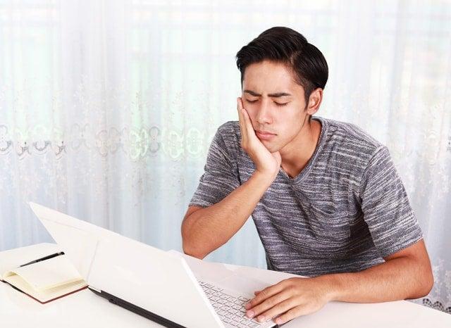 悩みながらパソコンをしている男性