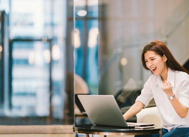 ガッツポーズを市ながらしながらパソコンを見る女性