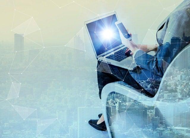 ビジネス女性がネットに繋がったスマホとパソコンを触るイメージ
