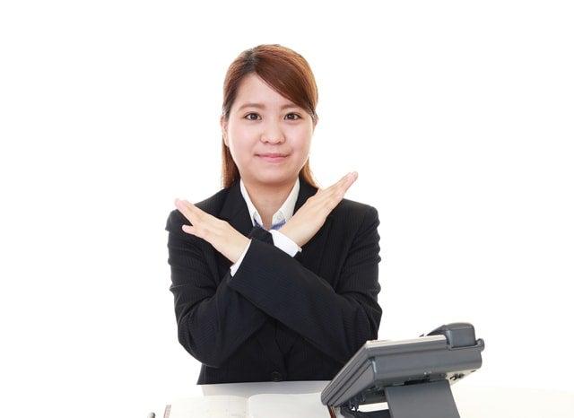 胸元で罰点をを作る女性と電話機