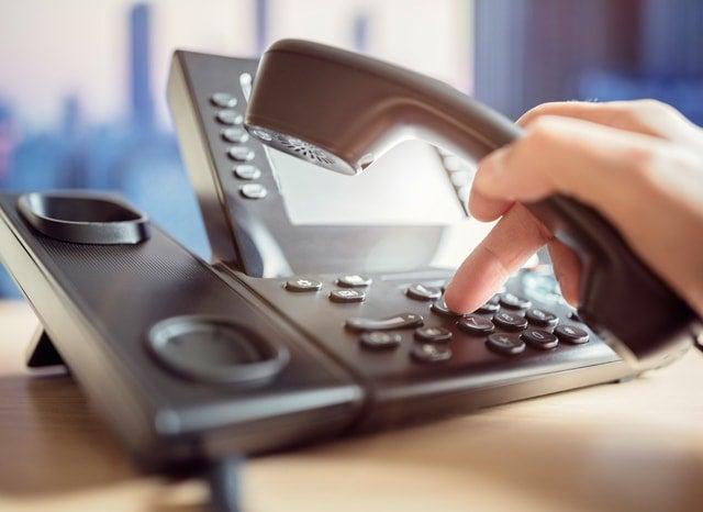 黒の固定電話をかける人