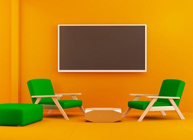 オレンジ色の部屋にあるテレビといす