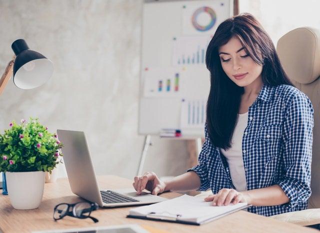 パソコンをしながら資料を見る女性