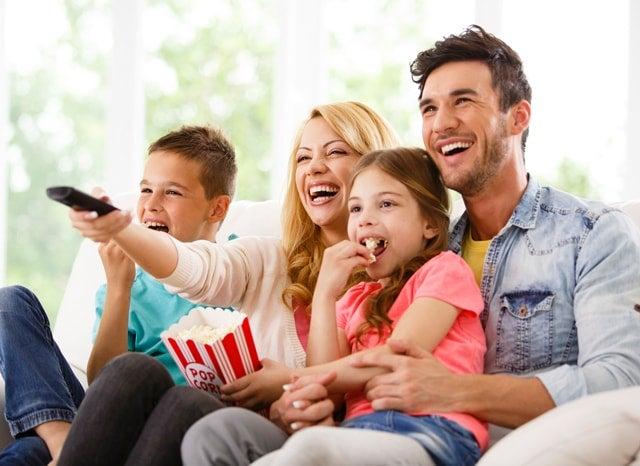 座ってお菓子を食べながらテレビを見る家族