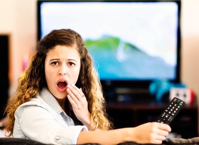 テレビのリモコンを持ちながら驚く女性