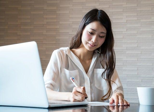パソコンを開きながら書類を記入する女性