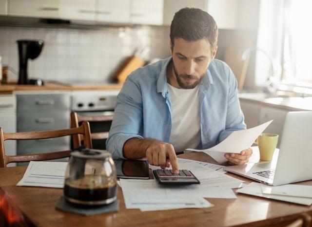 電卓で資料を見ながら計算する男性