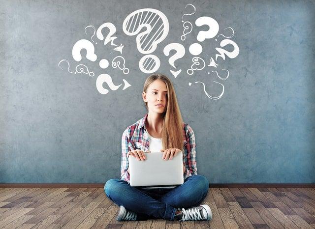 クエスチョンマークが書かれた黒板の近くに座っているパソコンを持った女性