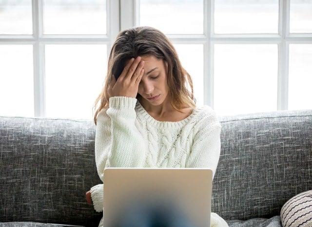 頭を押さえてパソコンをみる女性