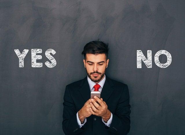 YES NOと書かれた黒板の間でスマホをする男性