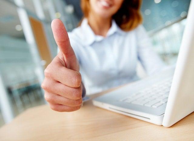 パソコンをしながらグッドサインをする女性
