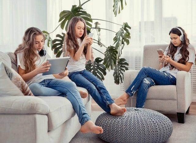 家の中でメディア機器を触る少女たち