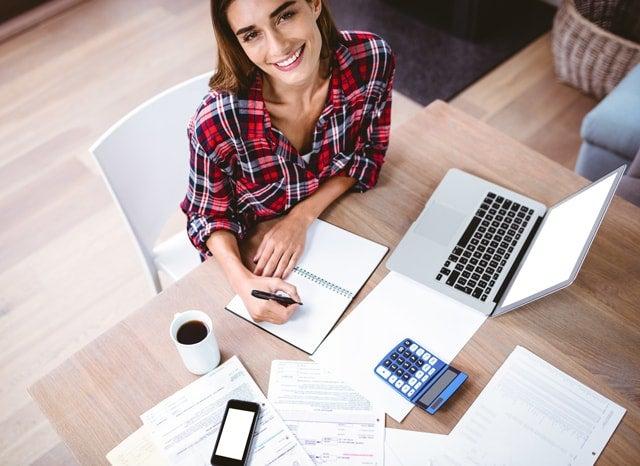 パソコンを開きながらノートにメモする女性