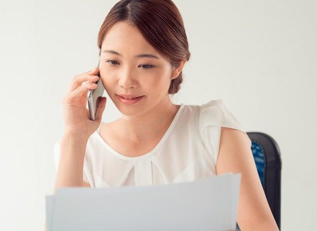 スマホで電話しながら資料を見る女性