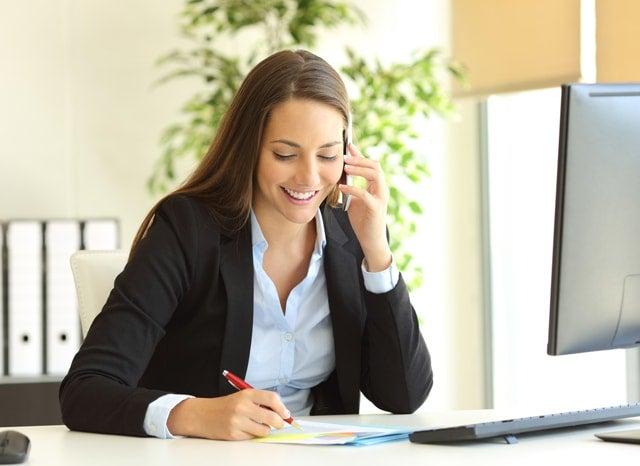 パソコンをしながらメモをする女性