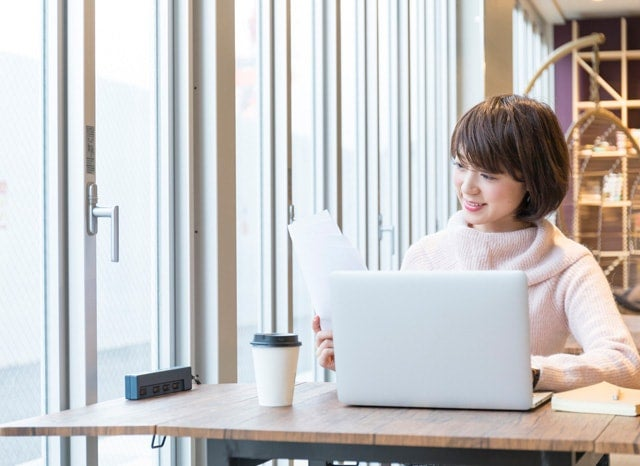 パソコンを開きながら資料を見る女性
