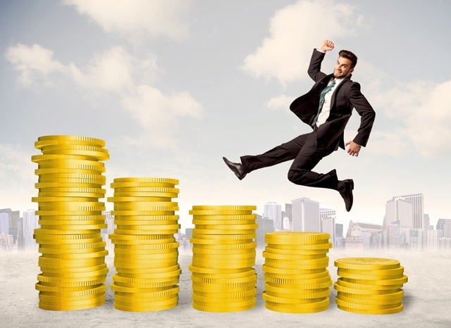 階段状に詰まれたコインを上る男性の様子