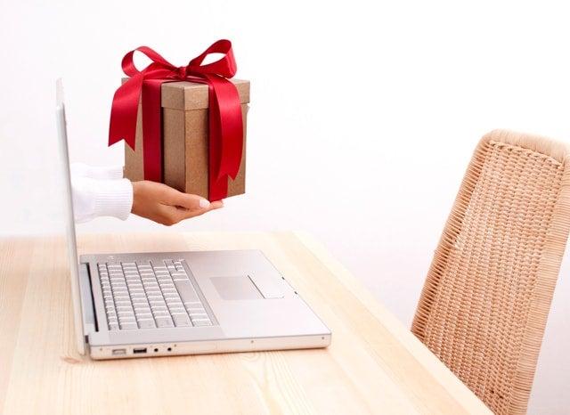 パソコンから出てくるプレゼントを持った人の手の様子