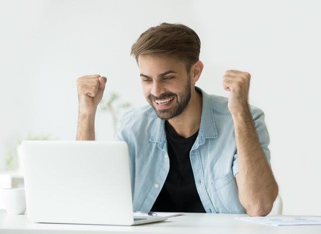 パソコンを見ながらガッツポーズする男性