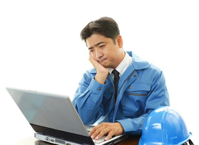 パソコンを見ながら困り顔の工事業者の男性