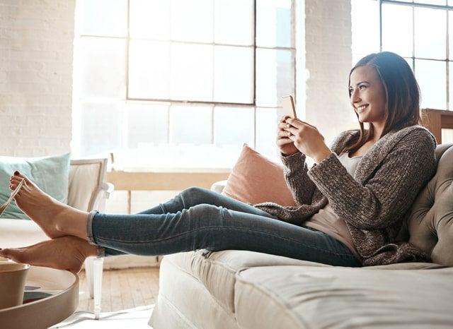 ソファーでスマホをする女性
