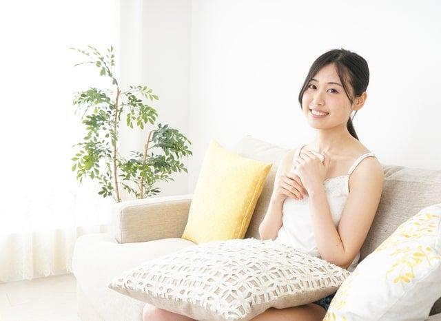 ソファーでスマホを両手で握って笑う女性