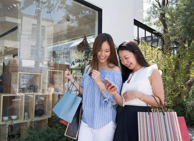 買い物袋を持ちながらスマホを見る女性