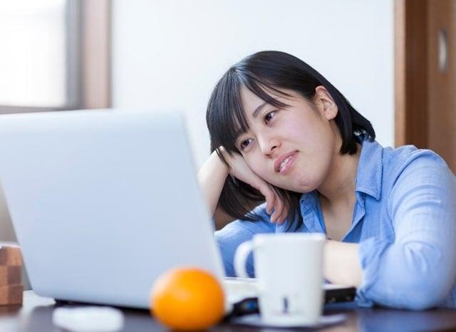 パソコンを見ながら不安な女性
