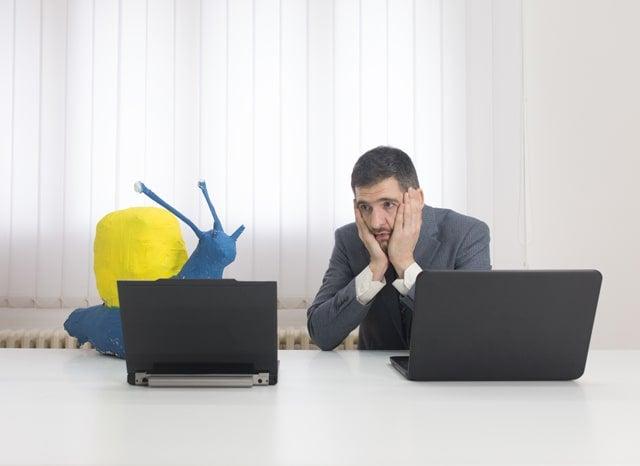 カタツムリの模型の近くに置かれたパソコンを不安そうに見る男性